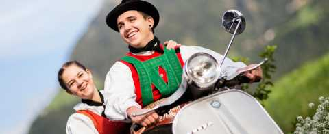 Riding Vespa scooters in South Tyrolean folk costumes